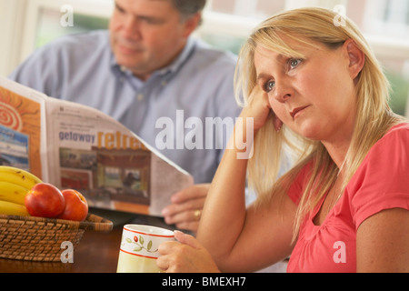 A Wife Being Ignored By A Husband Reading The Newspaper - Stock Photo