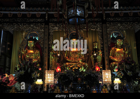 Three Golden Buddha Statues in the Great Hall of the Main Temple, Po Lin Monastery, Lantau Island, Hong Kong, China - Stock Photo