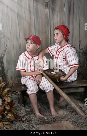 Two Boys Wearing Baseball Uniforms Sitting On A Bench - Stock Photo