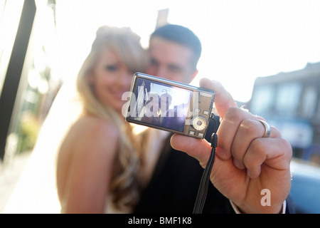 A Bride And Groom Taking A Self Portrait With A Camera - Stock Photo