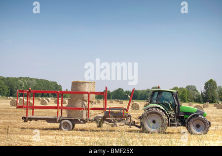 Tractor working on a field, collecting hay balls - Stock Photo