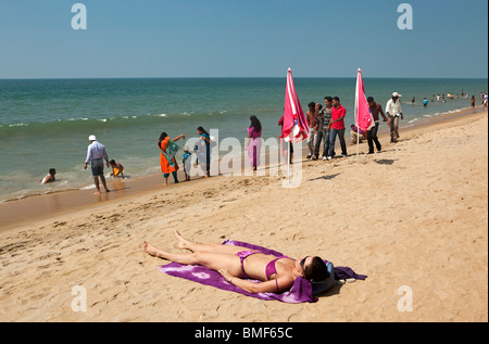India, Kerala, Vypeen Island, Cherai Beach western sunbather amongst fully dressed Indian visitors - Stock Photo