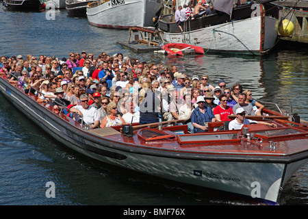 A canal tour cruise boat full of summer tourists is leaving Nyhavn on a sightseeing cruise in the port  of Copenhagen. - Stock Photo
