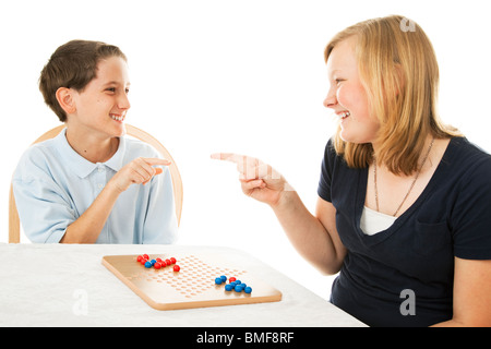 Brother and sister having fun playing board games. Isolated on white. - Stock Photo