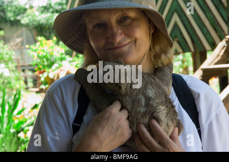 Woman holding a baby Brown-throated Three-toed Sloth in her arms, Amazon, Brazil