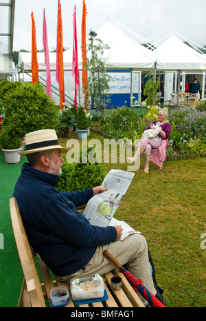Hatted man reading newspaper having lunch on a lated wooden bench with a woman and tents, flags in the background. - Stock Photo