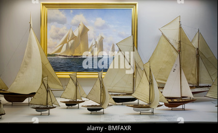 Maquettes of sailboats of different years and states of development with a schooner sailboat painting - Stock Photo