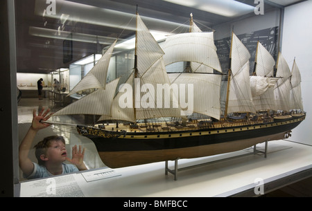 A boy admiring in awe at a XIX century clipper sailboat - Stock Photo