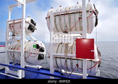 Inflatable liferafts in hard-shelled canisters and lifeboat on board of ferryboat, Europe - Stock Photo