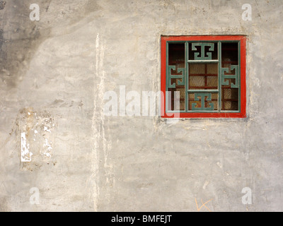 Small traditionally ornate square fan window on the house wall in hutongs, Beijing, China - Stock Photo