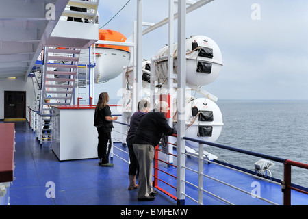 Tourists and inflatable liferafts in hard-shelled canisters and lifeboat on board of ferryboat, Europe - Stock Photo