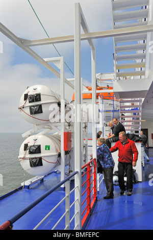 Tourists among inflatable liferafts in hard-shelled canisters and lifeboat on board of ferryboat, Europe - Stock Photo