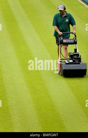 Groundsman cutting the lawn grass at All England Tennis Club, Wimbledon SW19, London. UK. - Stock Photo