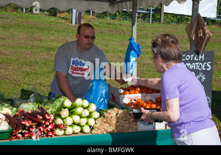 Woman buying fresh fruit and vegetables from a stall holder at a farmer's market, Clarkston, Glasgow, Scotland - Stock Photo