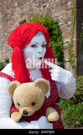 Women's Clkown Rag Doll Fancy Dress. A scary woman dressed  with Red Wig, and White Painted Face, at Muncaster Castle, - Stock Photo