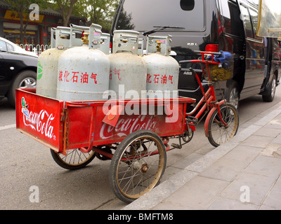 Cargo tricycle full of gas cylinders parked on the street in Beijing, China - Stock Photo