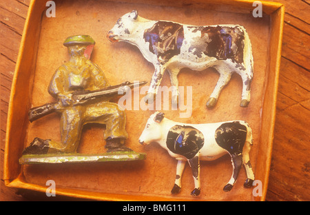 Close up in warm light of small cardboard tray containing scratched metal lead models of cow calf and infantryman - Stock Photo