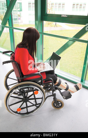 Young woman with leg in plaster - Stock Photo