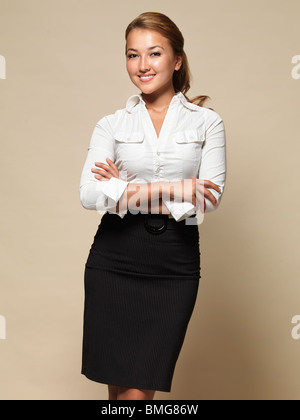 Portrait of a smiling young attractive businesswoman. Isolated on beige background. - Stock Photo