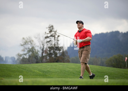 A Man Golfing On A Golf Course - Stock Photo