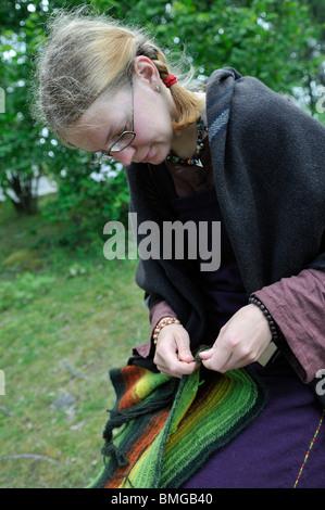 Girl in viking costume knitting in viking town Birka on Bjoerkoe Island, UNESCO World Heritage, Sweden - Stock Photo