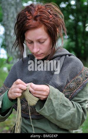 Woman in viking costume knitting in viking town Birka on Bjoerkoe Island, UNESCO World Heritage, Sweden - Stock Photo