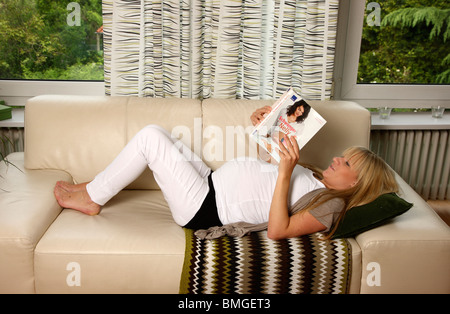 Pregnant young woman at home, reading a book about pregnancy. - Stock Photo