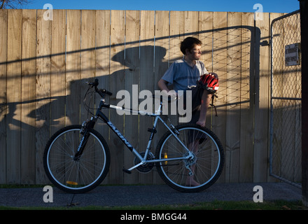 A boy with a bicycle against a wooden fence in the late afternoon, Auckland, New Zealand - Stock Photo