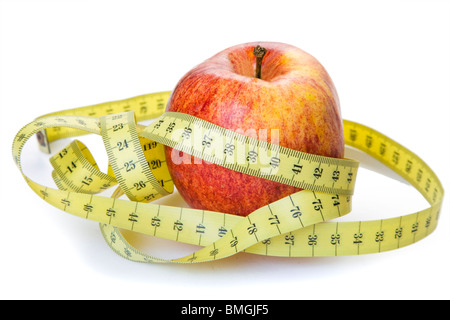 Red apple and a nest of measuring tape - Stock Photo