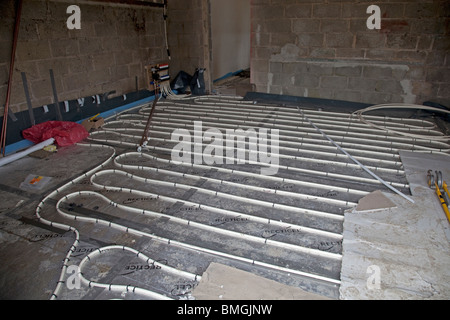 Installing underfloor heating pipes in new office building Cheltenham UK - Stock Photo