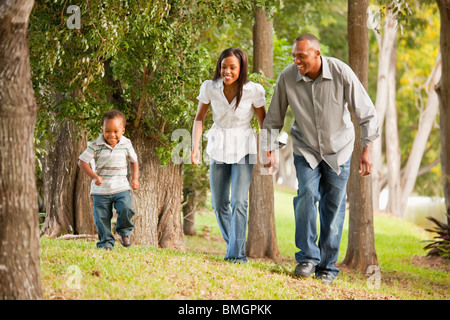 Fort Lauderdale, Florida, United States Of America; A Father And Mother With Their Young Son Walking Through A Park - Stock Photo