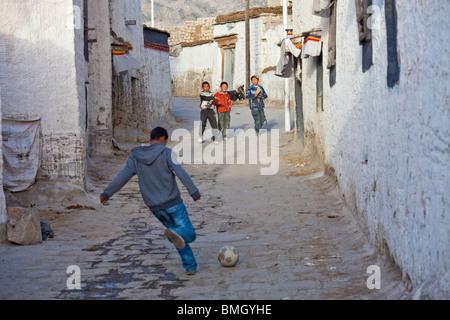 Boys kicking a football in Gyantse, Tibet - Stock Photo