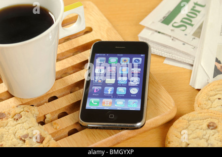 iphone on a desk with a cup of coffee - Stock Photo