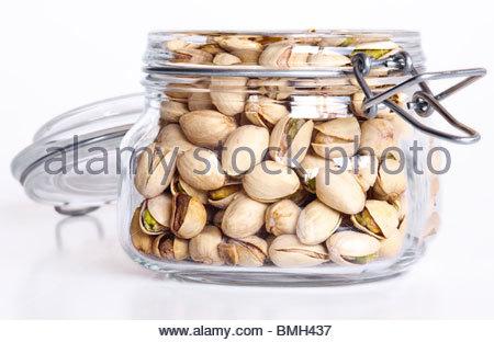 pistachios in airtight glass jar on white background - Stock Photo