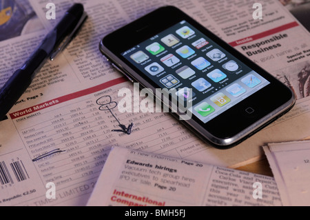 an iphone with a newspaper displaying stocks and share prices - Stock Photo