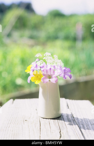 A jug filled with English wildflowers and garden flowers. - Stock Photo