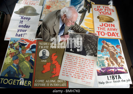 Roy Butler an expert on Militaria for the BBC's 'Antiques Road Show' inspects World War 1 and World War 2 posters. - Stock Photo
