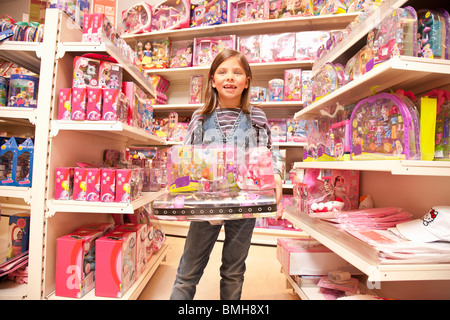 Little girl with pink toys - Stock Photo