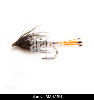 Black pennell trout fishing fly isolated on a white studio background. - Stock Photo