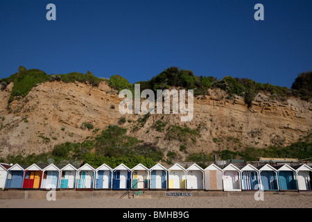 Row of bright beach huts under the cliff on Swanage beach. - Stock Photo