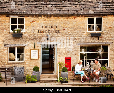 A couple having tea outside the Old Post Office in the Gloucestershire Cotswold village of Guiting Power, England, - Stock Photo