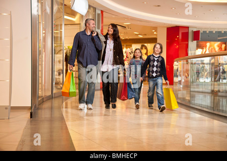 Family walking through shopping center - Stock Photo