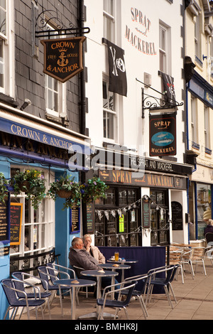 UK, England, Devon, Brixham Harbour, customers at pavement tables outside quayside pub restaurants - Stock Photo