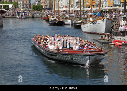 A canal tour cruise boat full of summer tourists leaving Nyhavn on a sightseeing cruise in the port of Copenhagen - Stock Photo