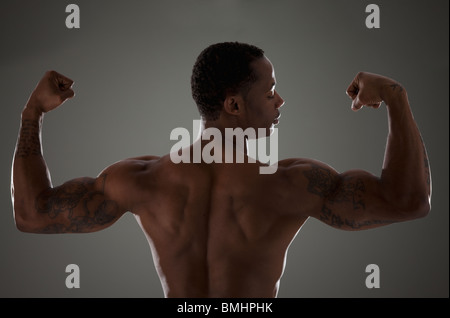 Physically fit man flexing his triceps - Stock Photo