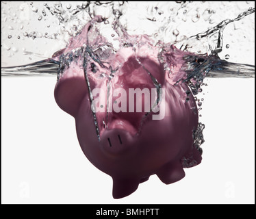 Piggy bank sinking in water - Stock Photo