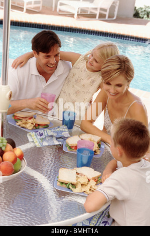Family eating lunch by the pool - Stock Photo