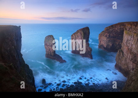 The Elegug Stacks just before dawn on a winter's morning along the Pembrokeshire Coast Path in Wales - Stock Photo