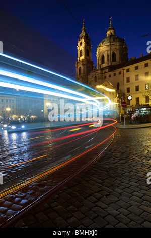 Light trails from a streetcar (Tramvaj) pulling into a stop in front of St Nicholas Cathedral in Lesser Town, Prague - Stock Photo