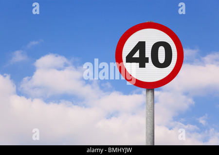 A round roadsign with the number 40 on it against a blue cloudy sky. - Stock Photo